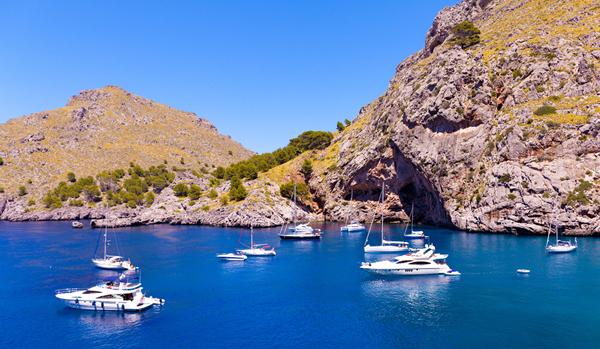 Sailing boats on the rugged coast of Mallorca